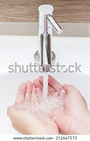 Stainless Steel Faucet with hand - stock photo