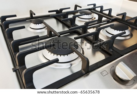 stainless steel gas hob detail on white stone worktop - stock photo