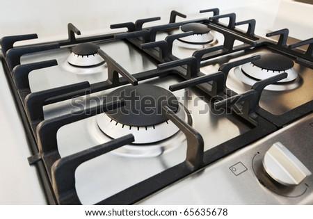 stainless steel gas hob detail on white stone worktop - stock photo