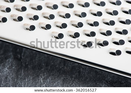 Stainless steel grater in close-up. Kitchen appliance used for grating in food preparation. - stock photo