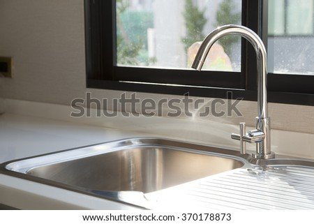Stainless steel kitchen faucet and sink - stock photo