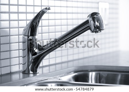 Stainless steel kitchen faucet and sink with tile backsplash - stock photo