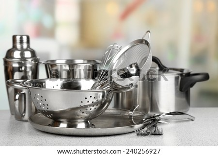 Stainless steel kitchenware on table, on light background - stock photo