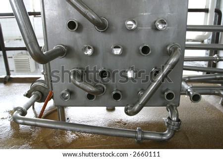 stainless steel pipes and valves in modern dairy plant - stock photo