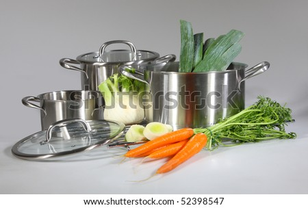 Stainless steel pots and pans isolated on gray background - stock photo