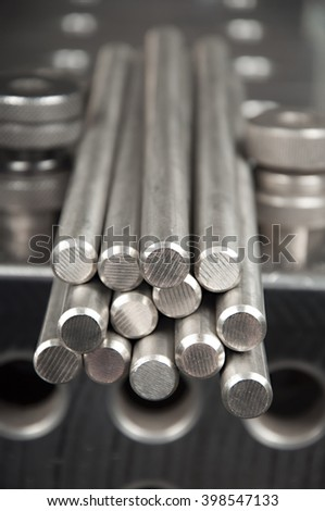 stainless steel rods on a welding table - stock photo