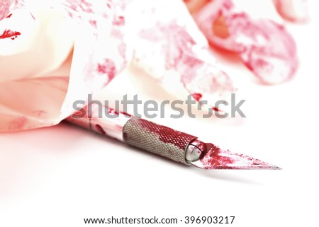 Stainless steel scalpel with blood and rubber gloves - selective focus on tip of blade - stock photo