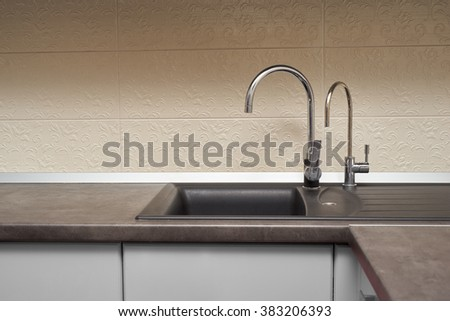 stainless steel sink and faucet in kitchen - stock photo