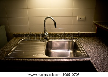 Stainless steel sink on top granite - stock photo