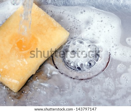Stainless steel sink plug hole close up with water - stock photo