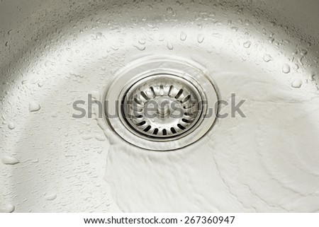 Stainless steel sink with water droplets. - stock photo