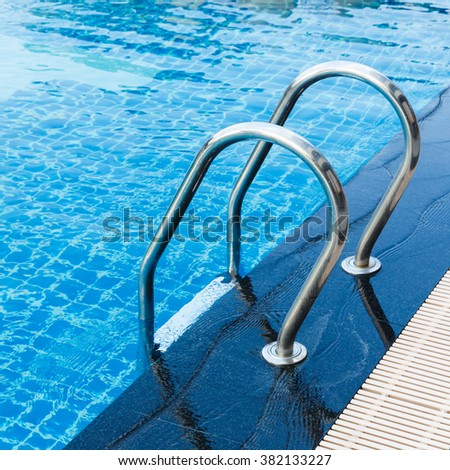 Stainless steel swimming pool hand rails - stock photo
