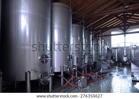 Stainless steel wine vats in a row inside the winery - stock photo