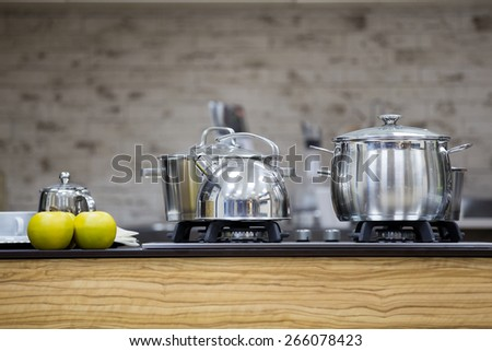 stainless utensils on gas cooker and apples - stock photo