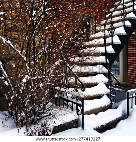 Staircase covered by snow during a sudden snowstorm in Montreal, Canada. - stock photo