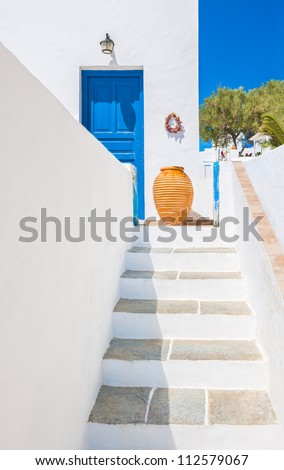 Staircase leading to an entrance with ceramic vase from the beautiful island of Sifnos, Greece - stock photo