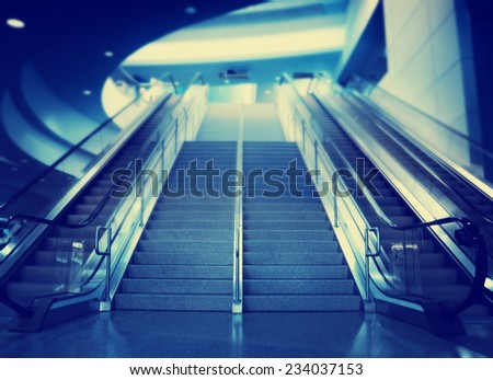 stairs and an escalator at an airport toned with a retro vintage instagram filter effect - stock photo