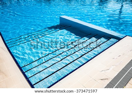 Stairs clear blue swimming pool background - stock photo