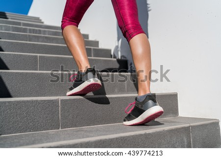 Stairs climbing running woman doing run up steps on staircase. Female runner athlete going up stairs in urban city doing cardio sport workout run outside during summer. Activewear leggings and shoes. - stock photo