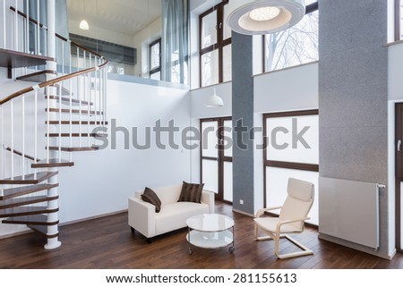 Stairs in spacious living room in contemporary mansion - stock photo