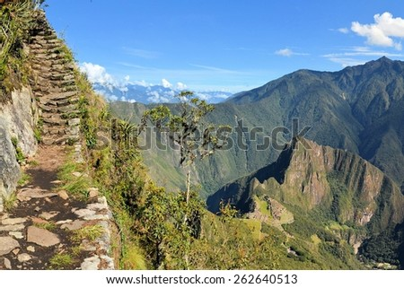 Stairs of an Inca trail up Macchu Picchu mountain with the lost city way below. Machhu Picchu is the famous lost city of the Incas near the river Urubamba located in the region of the sacred valley of - stock photo