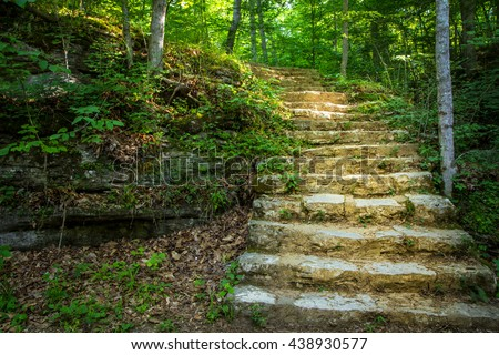 Stairway To Heaven. Winding stone stairway encased in light disappears into a lush green forest. Carter Caves State Park. Olive Hill, Kentucky. - stock photo
