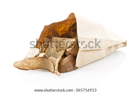 Stale bread in paper bag on white background - stock photo