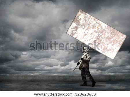 Stalker in gas mask with blank banner. Place for your text - stock photo