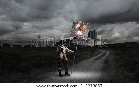 Stalker in gas mask with precaution danger sign - stock photo