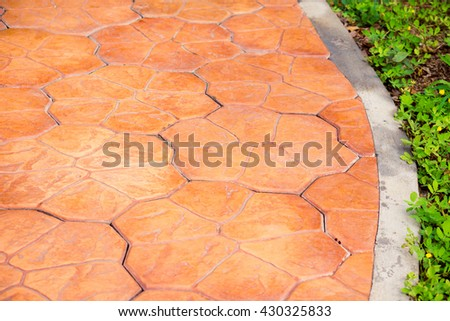 Stamp concrete texture pattern and background, Green meadow divided by rough stone walkway,Stamped concrete.Close up stamp concrete. - stock photo