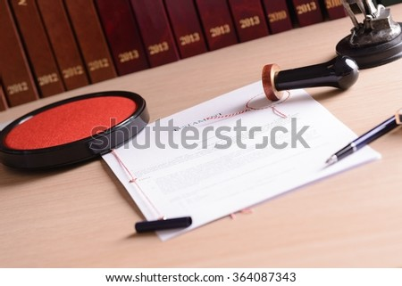 Stamp of notary public on testament. Notarial acts in the background. - stock photo