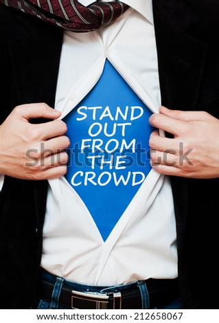 Stand out from the crowd concept. Businessman showing a superhero suit underneath his shirt with a business message text wording on it. - stock photo