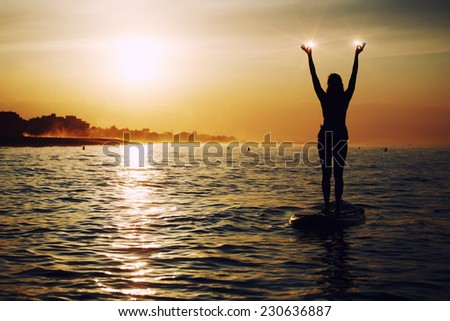 Stand up paddle board yoga performed by beautiful woman with bright sunset on background, yoga training in harmony with nature, silhouette of yoga woman holding lights in the hands, spiritual concept - stock photo