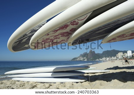 Stand up paddle long board surfboards stacked on Ipanema Beach Rio de Janeiro - stock photo