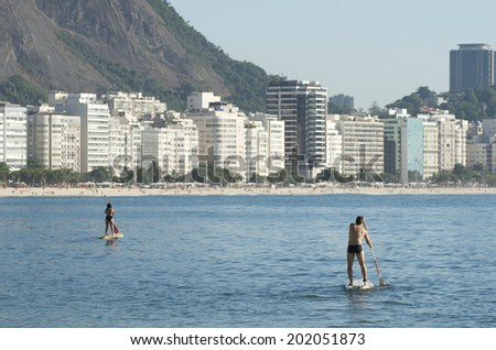 Stand up paddle surfers on calm seas at Copacabana Beach Rio de Janeiro Brazil - stock photo