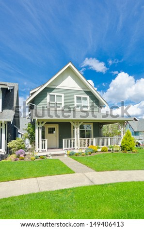 Standard house with nicely trimmed front yard, lawn in a residential neighborhood. Vancouver Canada. - stock photo