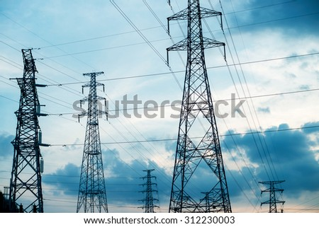standard overhead power line transmission tower at sunset. - stock photo