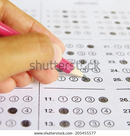 Standardized test form with answers bubbled in and a pencil  - stock photo