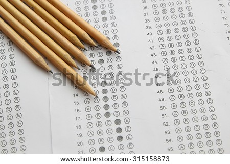 Standardized test form with answers filled in and a pencil, focus on answer sheet - stock photo