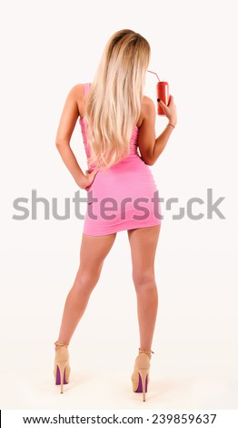 Standing beautiful woman in pink dress with drink. - stock photo