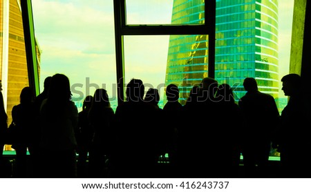 Standing business people silhouette. crowd persons inside modern building with wide blue enter hall window in Moscow city building skyscraper - stock photo