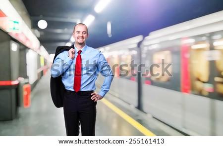 standing caucasian businessman and train - stock photo