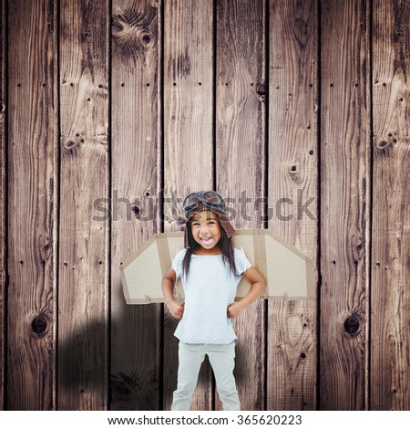 Standing girl with fake wings pretending to be pilot against wooden planks background - stock photo
