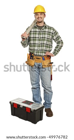 standing handyman with spirit level isolated on white - stock photo