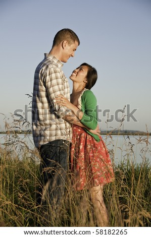 Standing in tall grass is a mixed race couple arm in arm. - stock photo