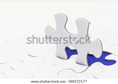 Standing jigsaw revealing blue background. Selective focus - stock photo