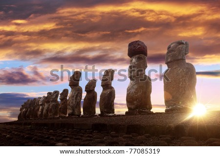 Standing moai in Easter Island against rising sun and orange sky - stock photo
