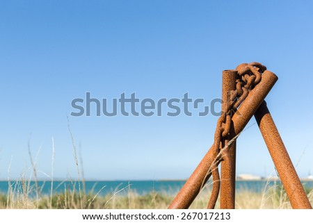 Standing rusty iron pipe and chain with Bluff port in background. The pipe stand has been arranged to lift or hold heavy items and has been left to rust in the yard. - stock photo