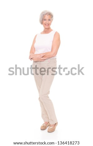Standing senior woman in front of white background - stock photo