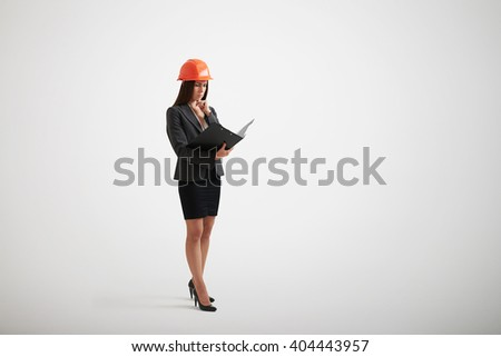 Standing woman in formal wear and construction helmet familiarize with the materials in black folder holding her hand near chin - stock photo
